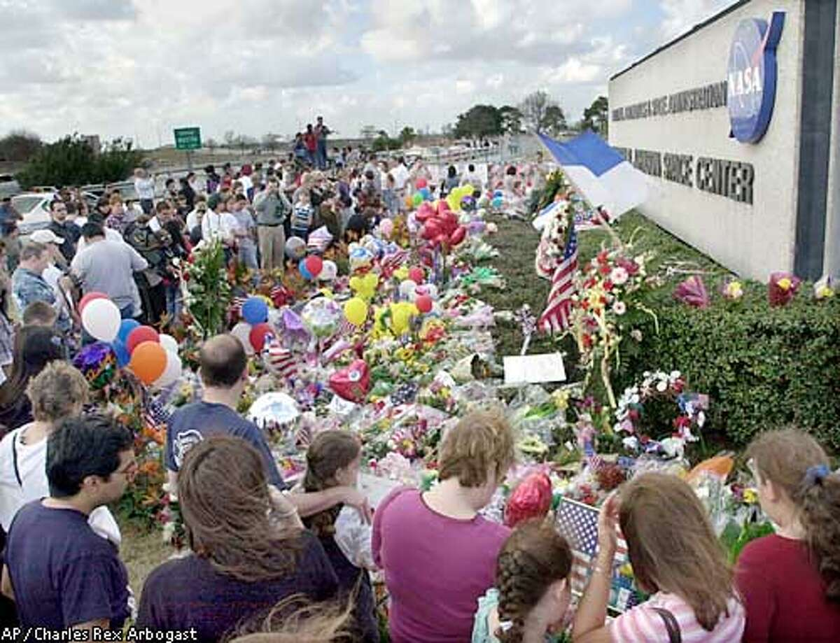 Mourners visit the main gate of the Johnson Space Center bringing memorial items for the family and crew of Columbia in Houston, Sunday, Feb. 2, 2003. Authorities used horses and satellite gear Sunday to search for more scorched pieces of Columbia across the Texas and Louisiana countryside. (AP Photo/Charles Rex Arbogast)