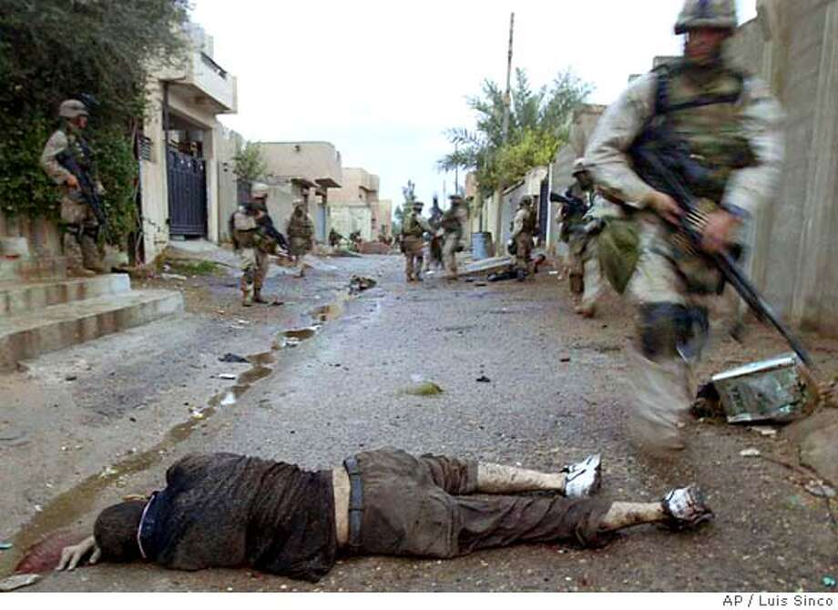 Members of Charlie Company of the First Marine Division, Eighth Regiment of the U.S Marines, walk past a dead insurgent in Fallujah, Iraq, Tuesday, Nov. 9, 2004. U.S. forces punched into the center of the insurgent stronghold, overwhelming bands of guerrillas in the street with heavy barrages of fire and searching house to house in a powerful advance on the second day of a major offensive. (AP Photo/Los Angeles Times, Luis Sinco) ** MANDATORY CREDIT, , NO FOREIGN, NO MAGS, LOS ANGELES DAILY NEWS OUT, OC REGISTER OUT, VENTURA COUNTY STAR OUT, INLAND VALLEY DAILY BULLETIN OUT, SAN BERNARDINO SUN OUT ** Photo: LUIS SINCO
