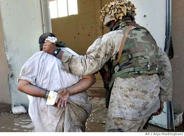 Unidentified soldier arrests an Iraqi man at the railroad station in Fallujah, Iraq, as U.S. Army and Marine units pounded the city with air strikes and artillery,Tuesday, Nov. 9, 2004. U.S. and Iraqi units roared into the insurgent stronghold of Fallujah through a breach near the railroad station at dawn Tuesday. (AP Photo/Anja Niedringhaus) Photo: ANJA NIEDRINGHAUS
