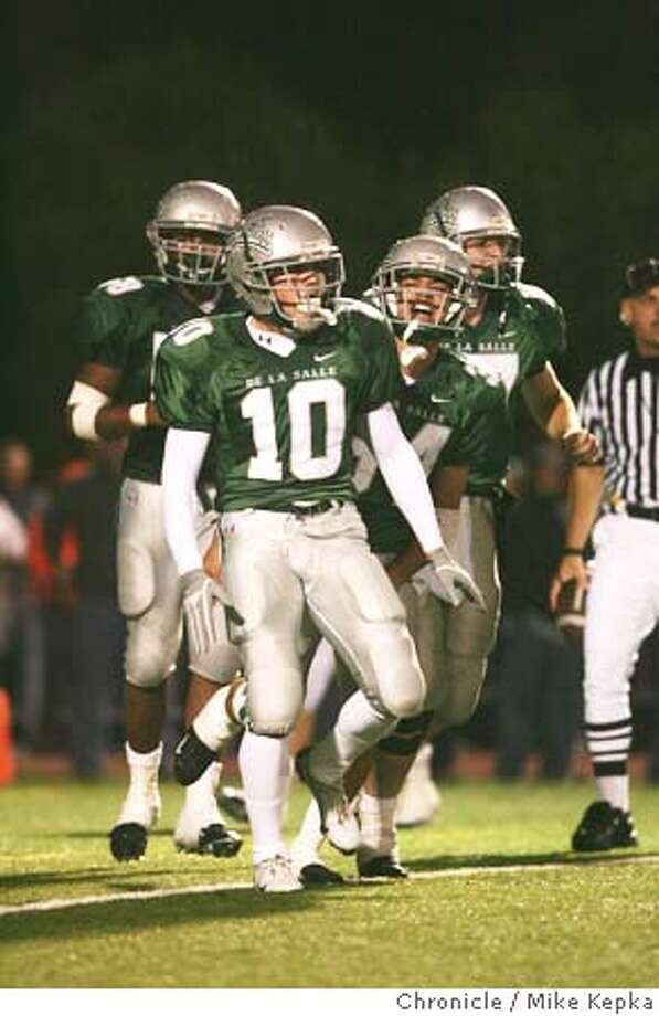 #10 Vincent Colvis is backed by an excited team after scoring in the 3rd period.  De La Salle High School vs. Pittsburg High at De La Salle Football stadium. 11/5/04  MIKE KEPKA/The Chronicle Photo: MIKE KEPKA