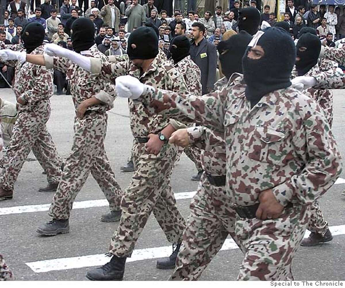 In Basra, Islamic militia men parade through the streets. Special to The Chronicle (no name)