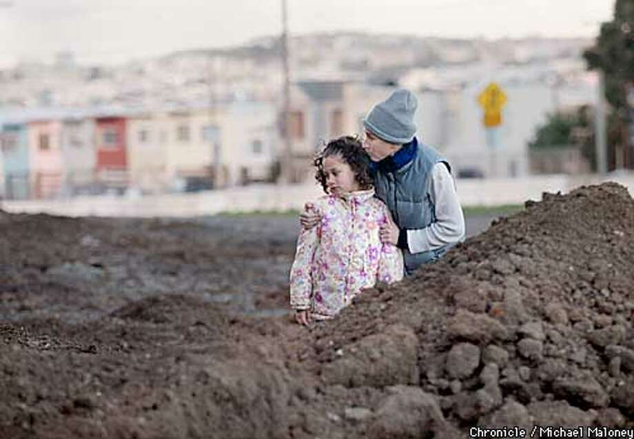 DIRT-C-27JAN03-MT-MJM  Sallou Asefaw (cq) and her daughter 7 year old Asmara Asefaw take a close look at dirt that was deposited without a permit in their Candlestick neighborhood. Both live in a house in the background on Jamestown Avenue. The dirt was from a motorcycle event at PacBell Park over the weekend.  CHRONICLE PHOTO BY MICHAEL MALONEY Photo: MICHAEL MALONEY