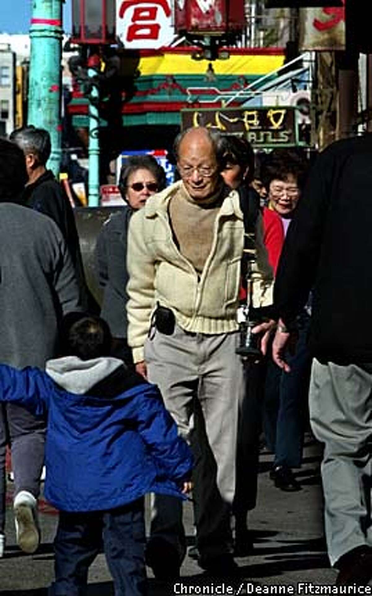 Benjamen Chinn smiles at a young boy as he walks through Chinatown with his camera over his shoulder. Chronicle photo by Deanne Fitzmaurice