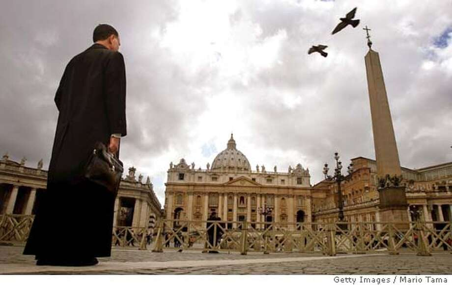 VATICAN CITY, VATICAN - APRIL 16: A priest stands in Saint Peter's Square as birds fly overhead April 16, 2005 in Vatican City. Cardinals under the age of 80 will start the conclave April 18 where a new pope will be chosen. (Photo by Mario Tama/Getty Images) Ran on: 05-01-2005  A priest stands in St. Peter's Square, where mourners at Pope John Paul II's funeral clutched Dan Brown's &quo;Angels & Demons,&quo; presumably planning to compare reality with surreality after the ceremony. Ran on: 05-01-2005  A priest stands in St. Peter's Square, where mourners at Pope John Paul II's funeral clutched Dan Brown's &quo;Angels & Demons,&quo; presumably planning to compare reality with surreality after the ceremony. Photo: Mario Tama