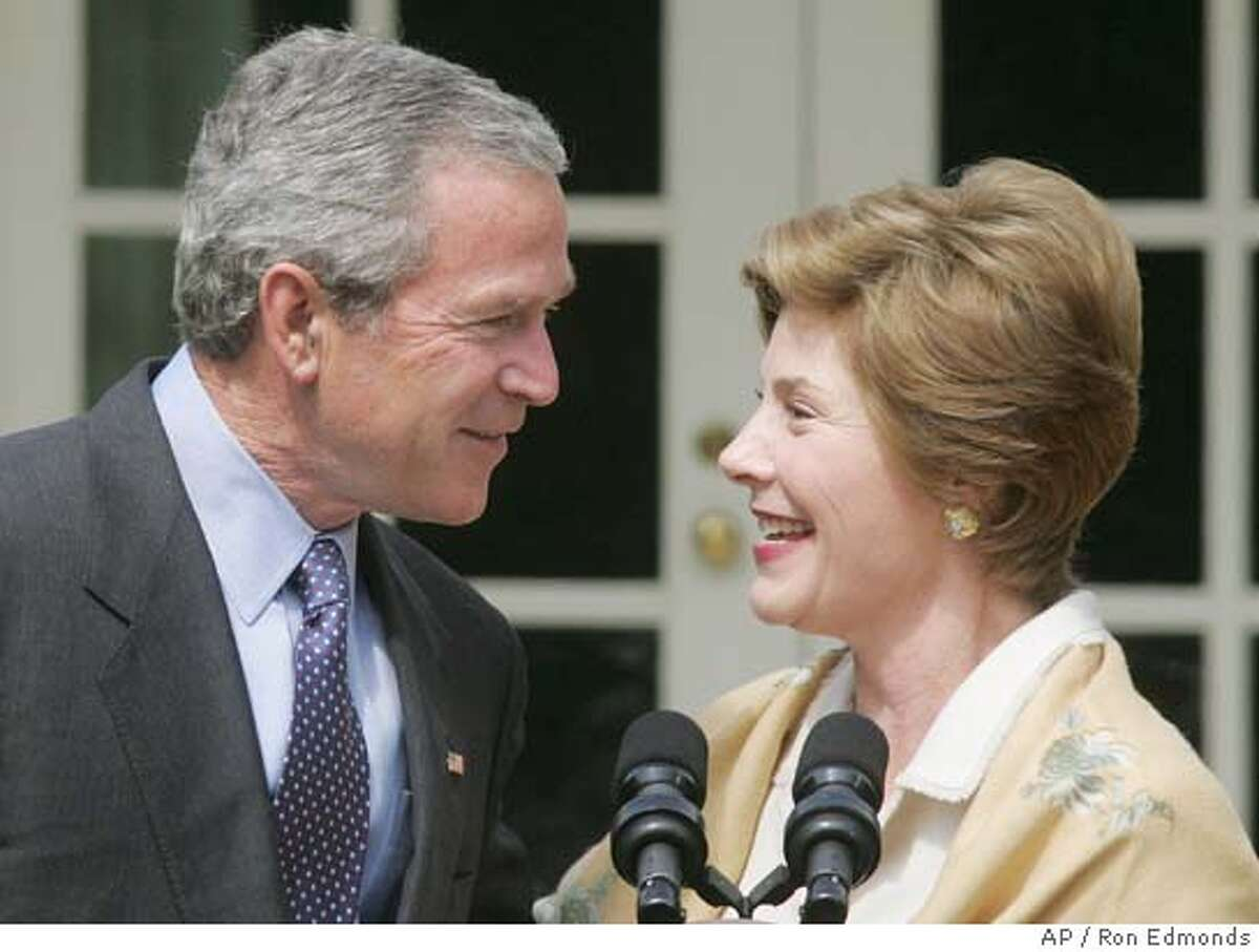 President Bush laughs with first lady Laura Bush, right, Monday, May 2, 2005, at the Preserve America Presidential Awards in the Rose Garden at the White House. Bush joked about the first lady Laura Bush's appearance at the annual White House Correspondents' Association dinner last Saturday night, where the president was toasted, but his wife stole the show. (AP Photo/Ron Edmonds)