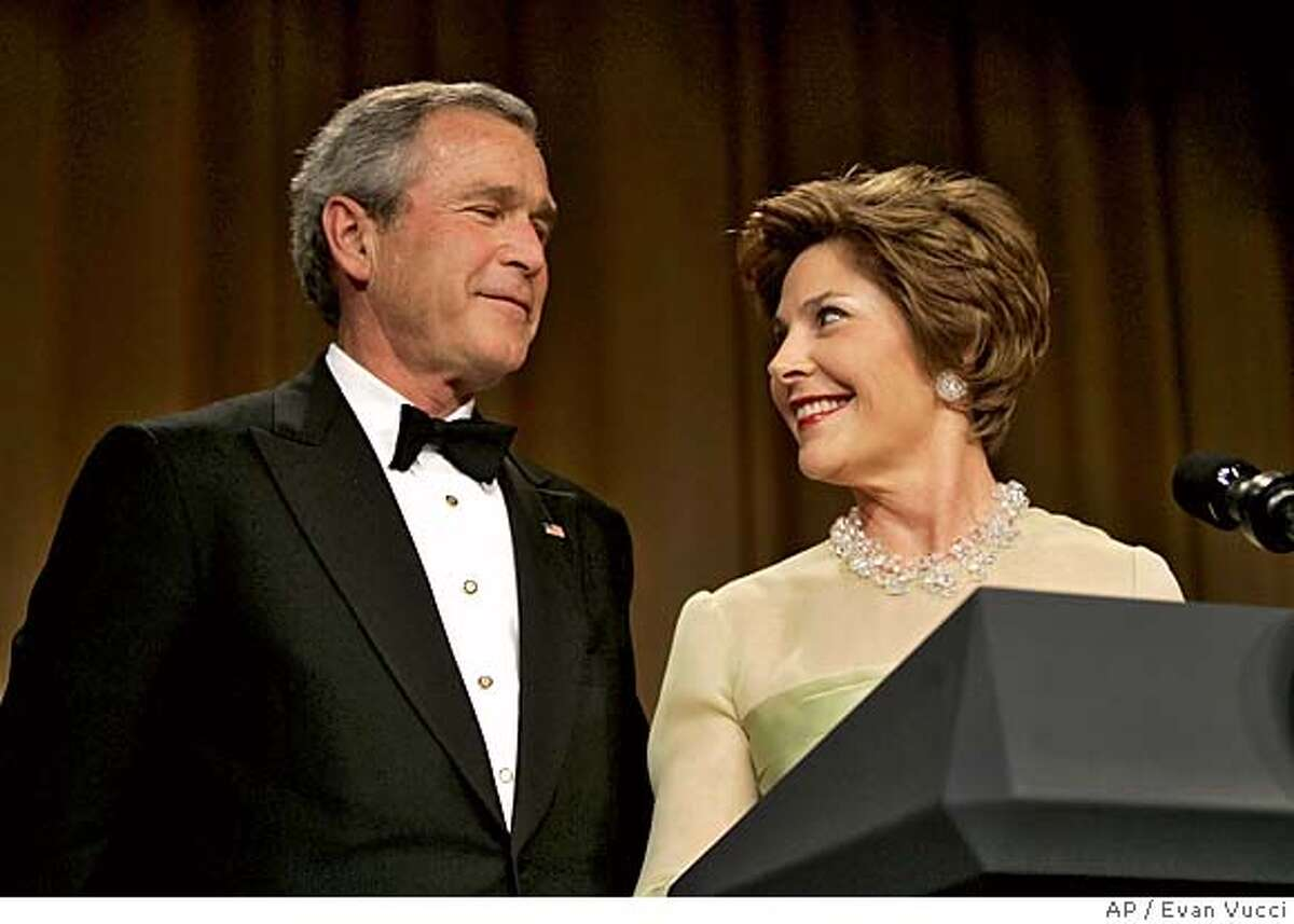 First lady Laura Bush stares at President Bush after taking the microphone away from him at the 91st annual White House correspondents dinner on Saturday, April 30, 2005 in Washington. (AP Photo/Evan Vucci)