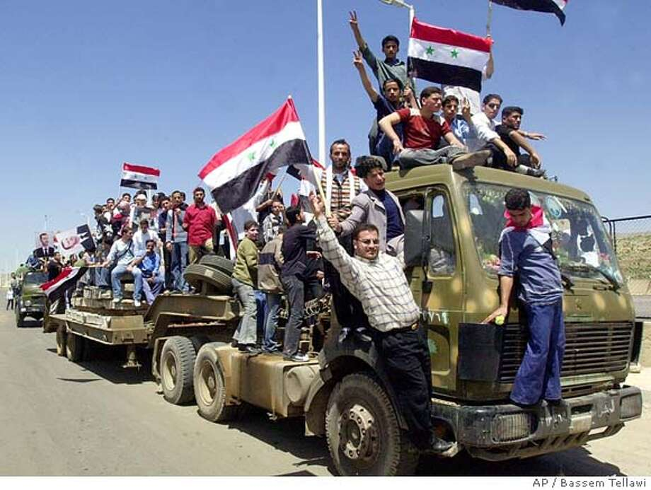 Syrians hold their national flags and portraits of their President Bashar Assad as they gather at Jdaidet Yabous a crossing point on the Syrian-Lebanese border, 45 kilometers (28 miles) west of Damascus, the Syrian capital, Tuesday, April 26, 2005 to celebrate the return of the last few hundred Syrian soldiers from Lebanon. (AP Photo/Bassem Tellawi) Photo: BASSEM TELLAWI
