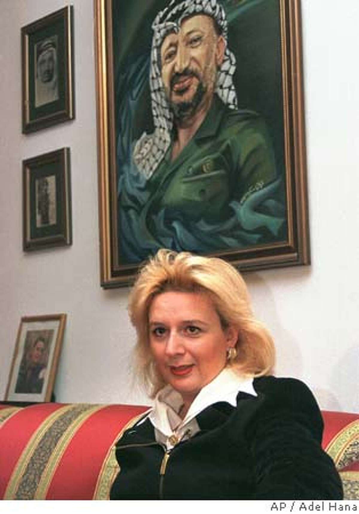 ** FILE ** Suha Arafat sits under a portrait of her husband, Palestinian leader Yasser Arafat, during an interview in this March 22, 1998 file photo in her Gaza home. French prosecutors have launched a money-laundering probe into suspected million-dollar transfers to accounts held by Suha Arafat, who lives in Paris, judicial officials said Wednesday Feb.11, 2004. (AP Photo/Adel Hana) also ran 02/16/2004 FILE Suha Arafats accounts at the Arab Bank and at French bank BNP are under scrutiny by prosecutors. Suha Arafat