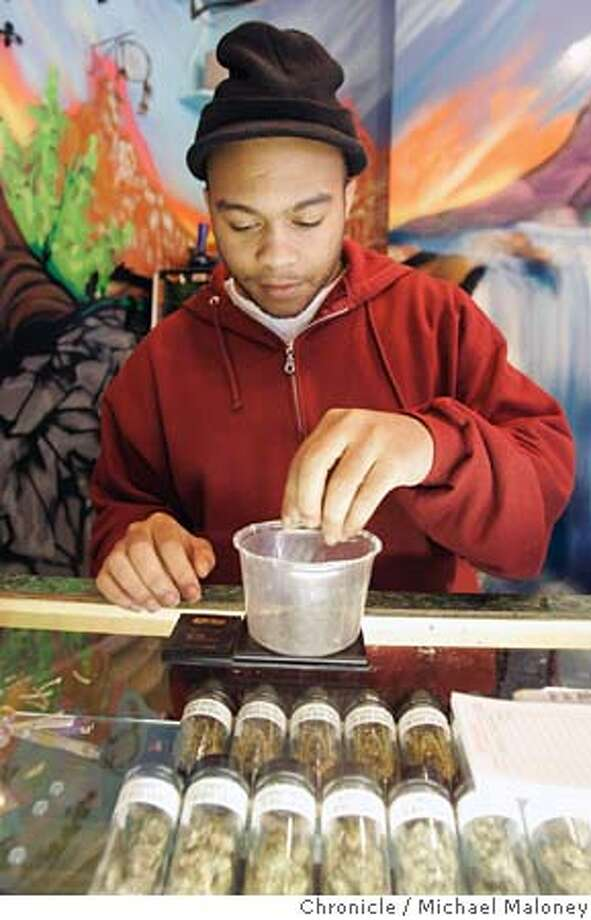 "POTCLUB_005_MJM.jpg  Alternative Herbal Health Services Facility employee Parrish ""Paradise"" Hughes weighs some pot for a customer. In the display case are various types of pot for sale.  The Alternative Herbal Health Services facility in the Haight is one of the legal pot clubs operating in the city. Customers show their medical pot ids to enter and like a retail store, have their choice of a wide variety of pot for sale. The store is also set up with couches and chairs to make the space available to those who want to smoke pot in the store.  Photo by Michael Maloney / San Francisco Chronicle MANDATORY CREDIT FOR PHOTOG AND SF CHRONICLE/ -MAGS OUT Photo: Michael Maloney"