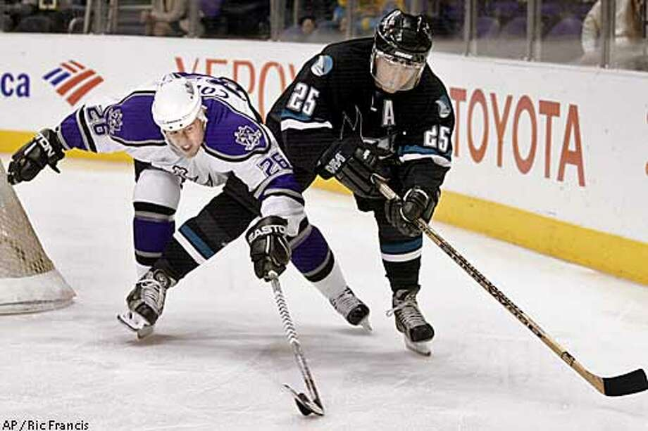 Los Angeles Kings' Joe Corvo (26) and San Jose Sharks' Vincent Damphousse (25) battle to control the puck in the first half Monday, Jan. 27, 2003, at Staples Center in Los Angeles. (AP Photo/Ric Francis) Photo: RIC FRANCIS