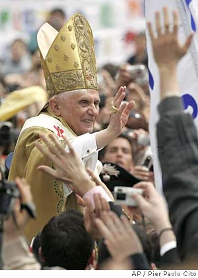 Pope Benedict XVI waves to the crowd as he rides on the popemobile through St. Peter's Square at the Vatican, Sunday, April 24, 2005, following his installment Mass. Dignitaries and an estimated 500,000 pilgrims, many of them from the pontiff's native Germany, arrived in Rome for the ceremony to formally install Pope Benedict XVI and offer the pontiff a major chance to set the tone for his papacy. (AP Photo/Pier Paolo Cito) Photo: PIER PAOLO CITO