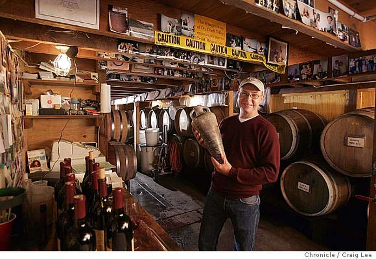 Rick Hutchinson, owner/winemaker of Amphora Wines in Healdsburg. Story is about people who make wines in garages or other small sites. Hutchinson is also a potter who makes amphorae (plural of amphora) -- wine vessels like those used by ancient Mediterraneans. He named his brand after his passion for pottery and wine. Photo of him holding one of his amphorae in his garage-like winery. Event on 10/23/04 in Healdsburg. Craig Lee / The Chronicle