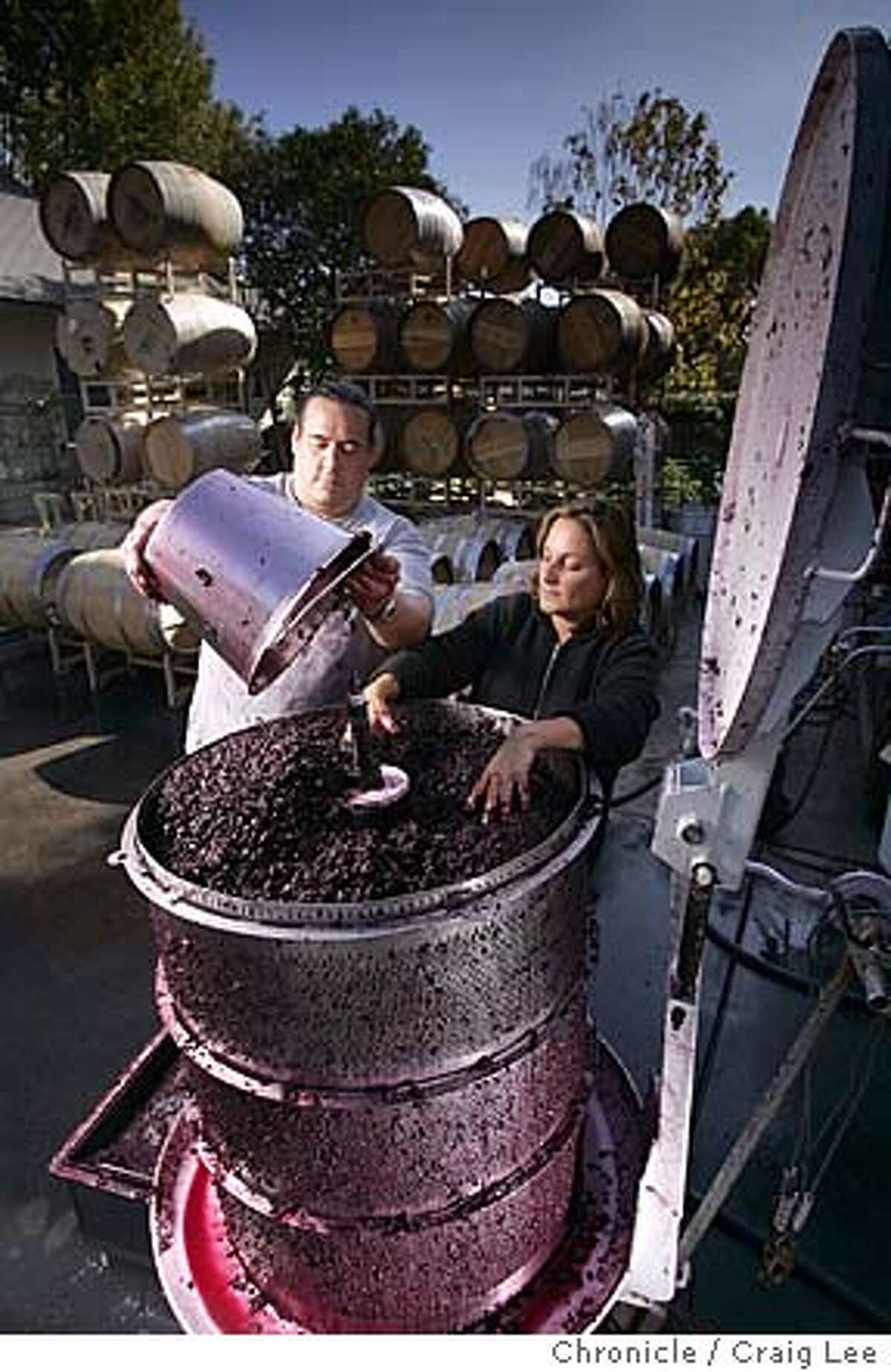 Merus Wines owners Mark Herold (left) and his wife, Erika Gottl (right) in their garage winery in Napa. Story is about people who make wines in garages or other small sites. Photo of them filling the basket bladder press. Event on 10/23/04 in Napa. Craig Lee / The Chronicle