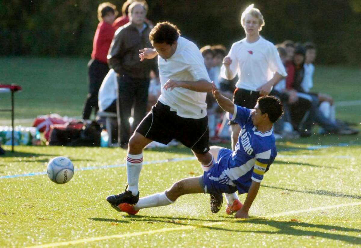 Greenwich midfielder Kevin Habibzadeh pushes through a tackle by Harding's Abner Duron as Greenwich High hosts Harding High Thursday afternoon, Oct. 29, 2009.