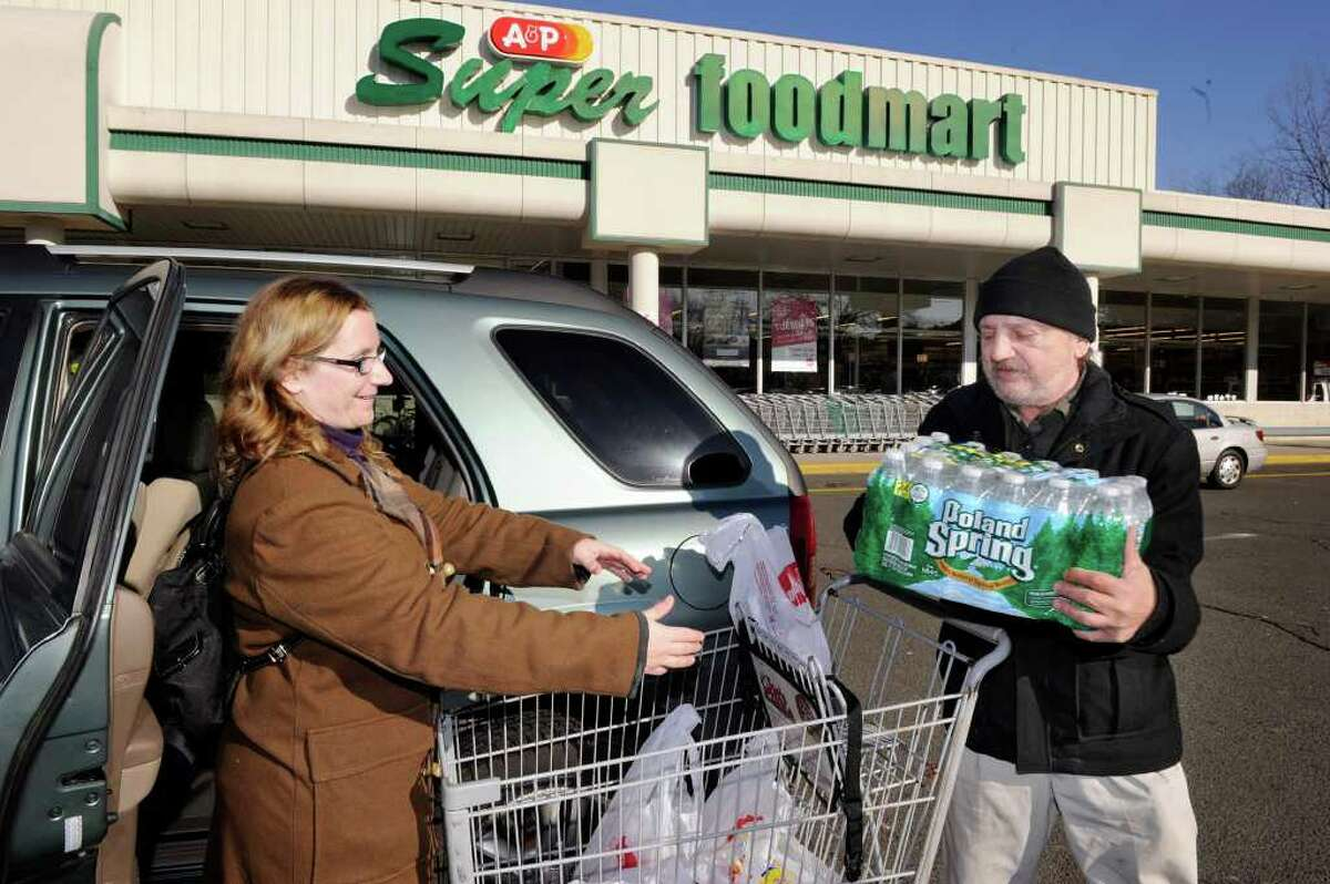 Danielle Rogotzke, of Danbury, left, and her father, Don Alfano, also of Danbury, load up their car after grocery shopping at the A&P on Main Street in Danbury Thursday. The company has announced that it will be closing the store. Photo taken Thursday, January 19, 2012.