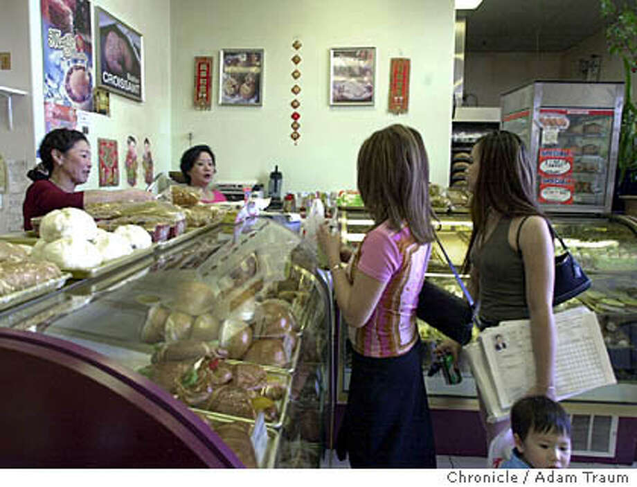 At the Century Bakery in the Grand Century Mall in San Jose Yi Lan, left helps customers, Julie Nguyen, right, and Kanty Huynh and J.C. Ly, 2. Second from left is Thuy Pham. The mall is a magent for Vietnamese/American-owned businesses and attracts many area Vietnamese residents. Photo by Adam Traum/The San Francisco Chronicle Photo taken on 04/19/05, in San Jose, CA.  Photo ADAM TRAUM / The San Francisco Chronicle Photo: ADAM TRAUM