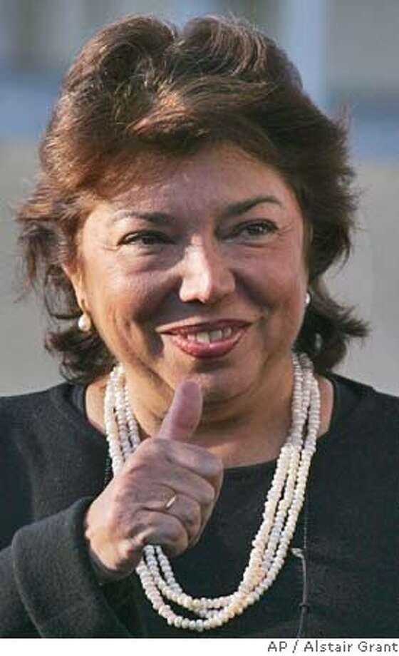 """Palestinian envoy to France Leila Shahid, gives the thumbs up to Arafat supporters prior to speaking to the media outside the military hospital where ailing Palestinian leader Yasser Arafat is receiving treatment in Clamart, outside Paris, Saturday Oct. 30, 2004. Shahid said Doctors have """"excluded for the time being any possibility of leukemia."""" (AP Photo/Alstair Grant) Photo: ALASTAIR GRANT"""