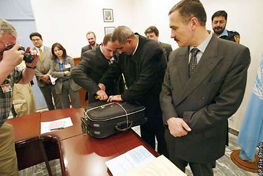Iraqi officials seal a suitcase destined for the United Nations Security Council which contains mass of documents detailing Iraq's nuclear, chemical and biological activities after handing out the documents to U.N. officials at the U.N. in Baghdad on Saturday, Dec. 7, 2002. The 12,000 pages declaration is to be flown to New York and Vienna Sunday. (AP Photo/Jerome Delay, Pool) Photo: JEROME DELAY
