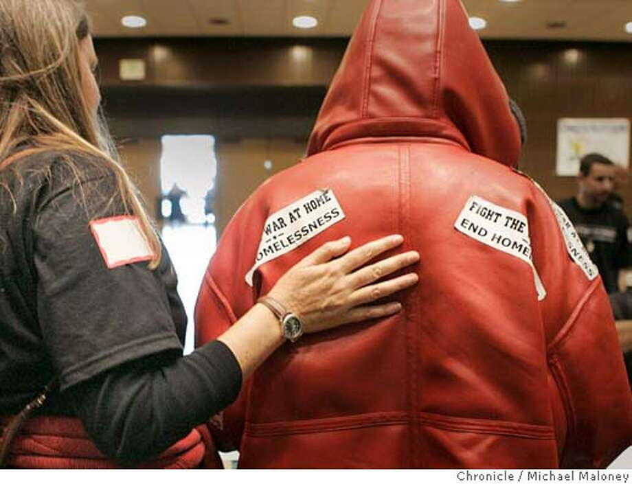 "HOMELESSCONNECT_065_MJM.jpg  Volunteer Katharyn (cq) Fenske gives a homeless man a reassuring pat on the back as he seeks medical help with bumper stickers on his back ""Fight the war at home, end homelessness.""  Katharyn (cq) Fenske (47 years old) of Mountain View is concerned about homelessness and doing her part to help - even if it means getting up hours before dawn to volunteer in San Francisco at Project Homeless Connect. Project Homeless Connect is a monthly muster of over 700 volunteers who help the homeless for a day, providing them with medical care, legal help, housing, food and other services. It is held at the Bill Graham Civic Auditorium and depends on volunteers like Fenske.  Photo by Michael Maloney / San Francisco Chronicle MANDATORY CREDIT FOR PHOTOG AND SF CHRONICLE/ -MAGS OUT Photo: Michael Maloney"