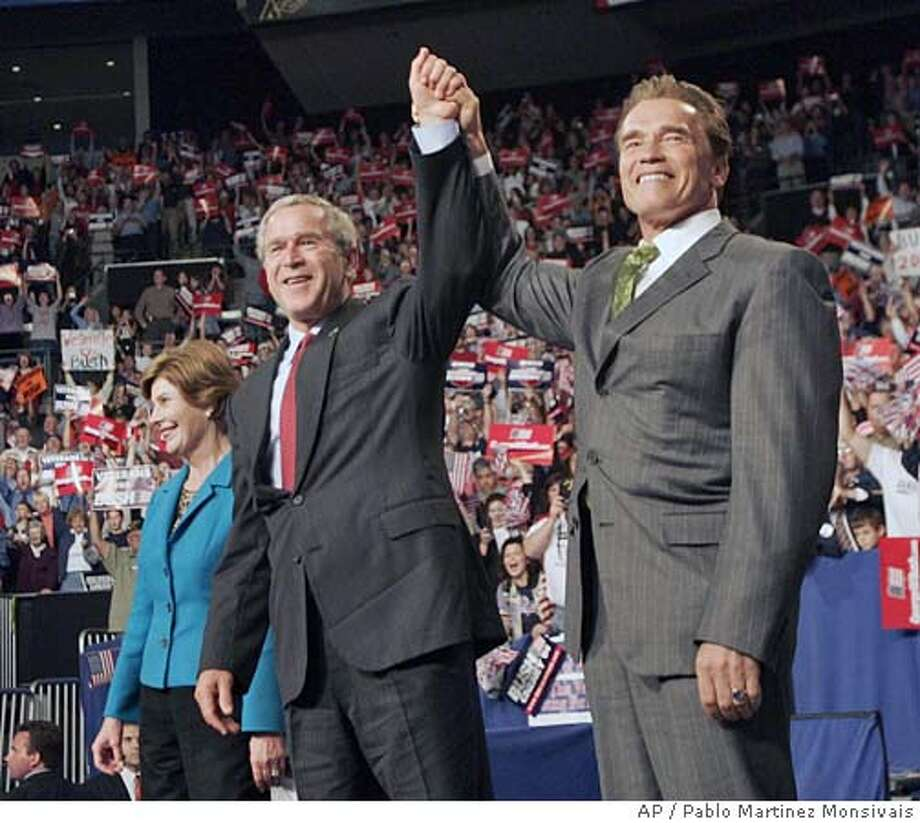 California Gov. Arnold Schwarzenegger, right, holds up the arm of President Bush, center, as introduces him and first lady Laura Bush, left, at a campaign rally Friday, Oct. 29, 2004 in Columbus, Ohio. (AP Photo/Pablo Martinez Monsivais) Photo: PABLO MARTINEZ MONSIVAIS