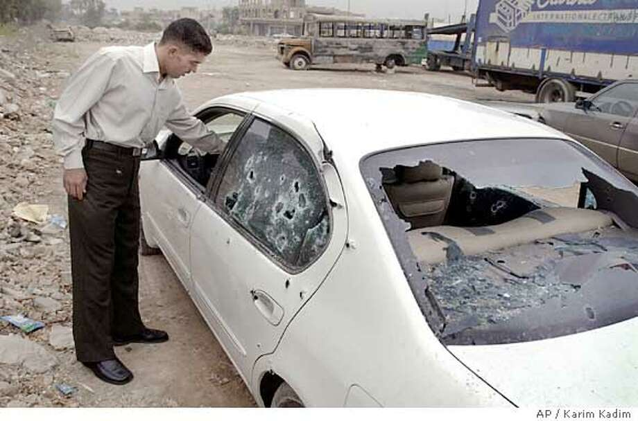 A security guard inspects the car of the deputy governor of Baghdad province, Hatim Kamil, after he was killed by gunmen who opened fire on his car in Baghdad, Iraq, Monday, Nov. 1, 2004, Iraqi authorities said. Two of his bodyguards were also wounded in the attack, officials said.(AP Photo/Karim Kadim) Ran on: 11-02-2004  A guard inspects the car in which the deputy governor of Baghdad province was killed. Ran on: 11-02-2004  A guard inspects the car in which the deputy governor of Baghdad province was killed. Photo: KARIM KADIM