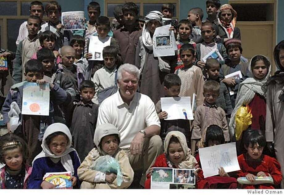 Photo of Budd MacKenzie with Afghan school children during his recent trip to Afghanistan. They are holding up photos and drawings from school children in Lafayette that he brought to Afghanistan. Photo by Walied Osman Photo: Walied Osman