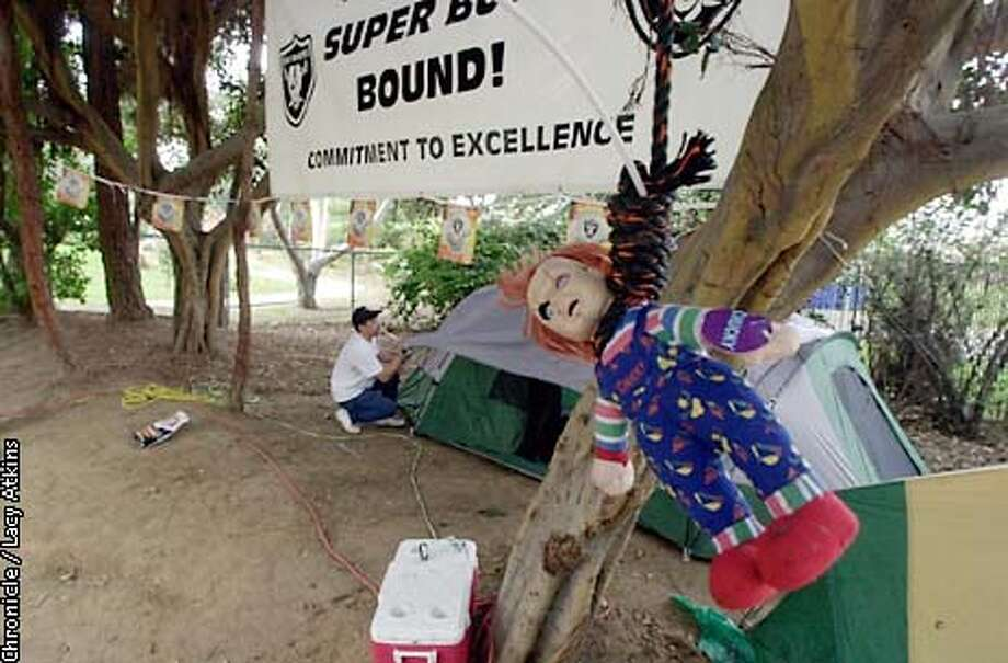 "Doug Keeter ,37yrs., of Jackson, Ca. put the rainfly on his tent at the campground in San Diego, Thursday Jan. 23, 03. Keeter and friends, fans from the Black Hole, have decorated their campsite with Raider banners and a hanging ""Chucky"" doll that they drug behind their truck from the Bay Area to San Diego for the Super Bowl.  San Francisco Chronicle Photographer Lacy Atkins Photo: LACY ATKINS"