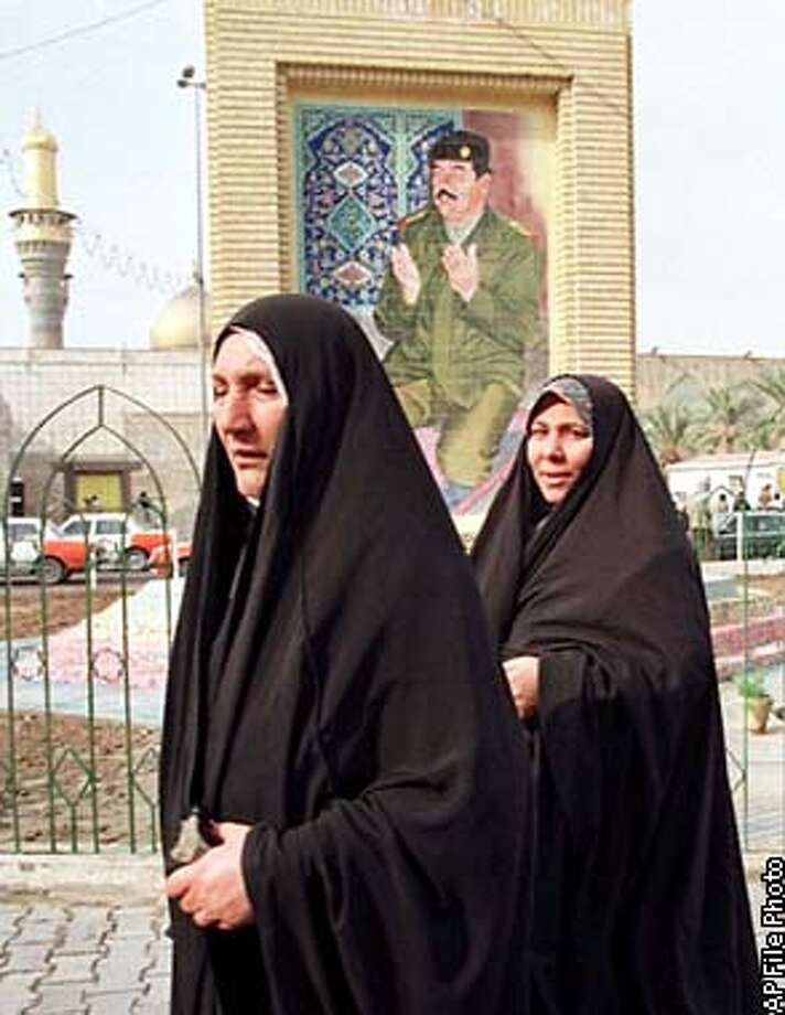 Iraqi women walk by a portrait of President Saddam Hussein in front of the Imam Musa Al-Kadum Mosque in the Kadhimiya district of Baghdad, Iraq Wednesday, Dec. 30, 1998. It seems few people at the U.N. sense an urgent need to figure out a future for U.N. weapons inspections in Iraq, at least not during the holidays or as long as Baghdad and Washington still trade fire and angry rhetoric. (AP Photo/Murad Sezer)
