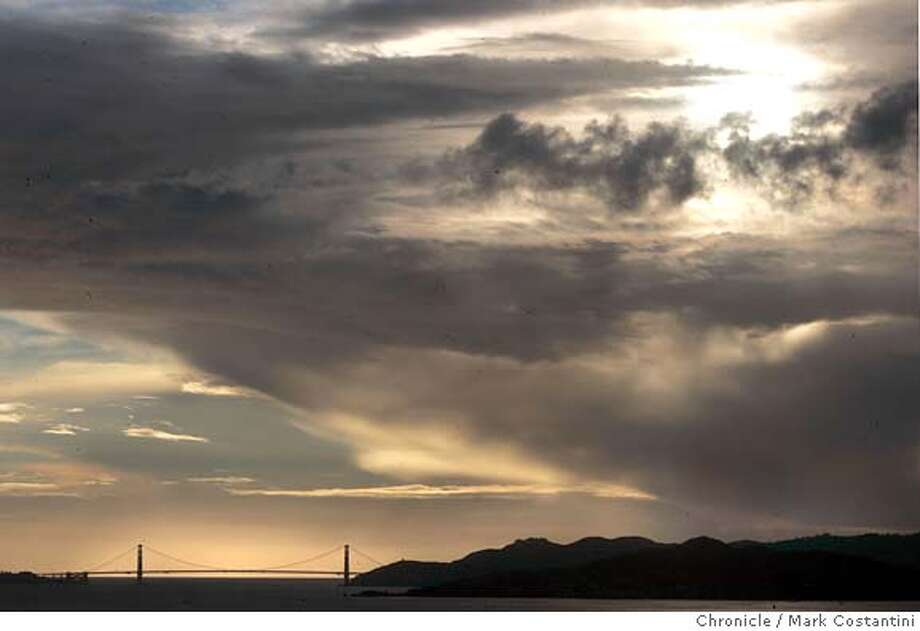 Clouds gather over the Goldent Gate Bridge at sunset. View is from Kensington.  Feature picture for East Bay page of Bay Area Section. 10/26/04 in Kensington.  S.F. Chronicle photo by Mark Costantini. Photo: Mark Costantini