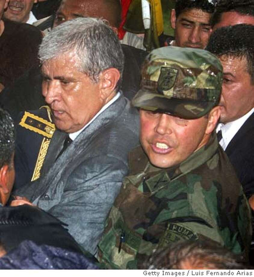 New Ecuador's President Alfredo Palacio tries to leave the CIESPAL building as he is being held by demonstrators after he was sworn in 20 April in Quito. Ecuador's controversial leader, Lucio Gutierrez, was placed under arrest Wednesday after Congress ousted him, the armed forces withdrew their support and a new president was named. The embattled Gutierrez left the Carondelet presidential palace just as the legislature named Vice President Alfredo Palacio as the new head of state. AFP PHOTO LUIS FERNANDO ARIAS (Photo credit should read LUIS FERNANDO ARIAS/AFP/Getty Images) Photo: LUIS FERNANDO ARIAS