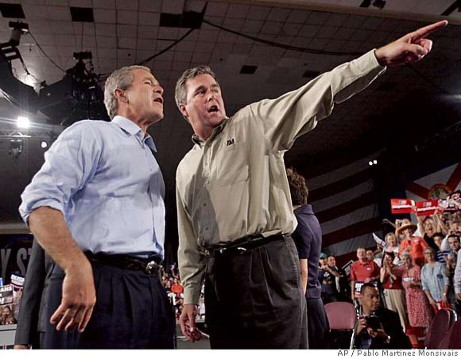 Florida Gov. Jeb Bush, right, points towards the crowd for his brother President Bush, left, at a campaign rally at the Coconut Grove Expo Center, Sunday, Oct. 31, 2004 in Coconut Grove, Fla. (AP Photo/Pablo Martinez Monsivais) Ran on: 11-01-2004  In church were President Bush, left, in Coral Gables, Fla., and Sen. John Kerry, right, in Dayton, Ohio. Bush was joined by his brother, Florida Gov. Jeb Bush, at a rally in Coconut Grove, above left, before heading to Ohio. Kerry greeted supporters in Manchester, N.H., above right, then went to Florida. Photo: PABLO MARTINEZ MONSIVAIS