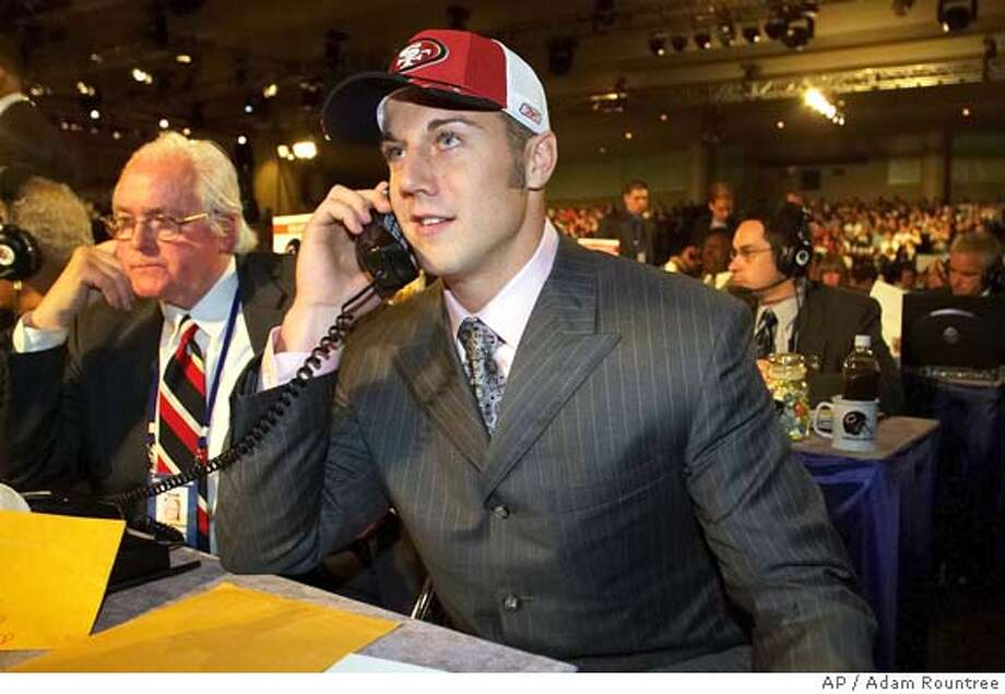 Alex Smith, a quarterback from Utah, talks on a phone at the San Francisco 49ers draft desk after being chosen as No. 1 overall pick by the 49ers in the 2005 NFL draft in New York on Saturday, April 23, 2005. (AP Photo/Adam Rountree) Photo: ADAM ROUNTREE