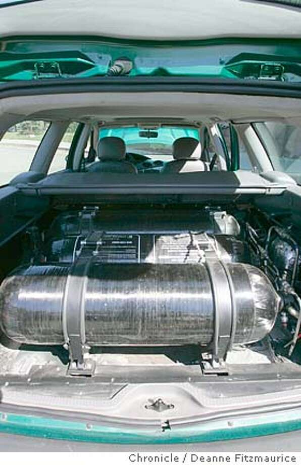 energy_544_df.JPG  Ford has built a test car which runs on hydrogen stores in this tank in the back of the car. Ford Motor Company is among the U.S. auto makers who are trying to improve fuel efficiency and address energy issues. Deanne Fitzmaurice / The Chronicle Ran on: 10-26-2004  A fleet of brand-new Ford Escape hybrid SUVs stands lined up ready for test drives at an outdoor auto show in San Mateo. MANDATORY CREDIT FOR PHOTOG AND SF CHRONICLE/ -MAGS OUT Business#Business#Chronicle#10/31/2004#ALL#2star#D6#0422386247 Photo: Deanne Fitzmaurice