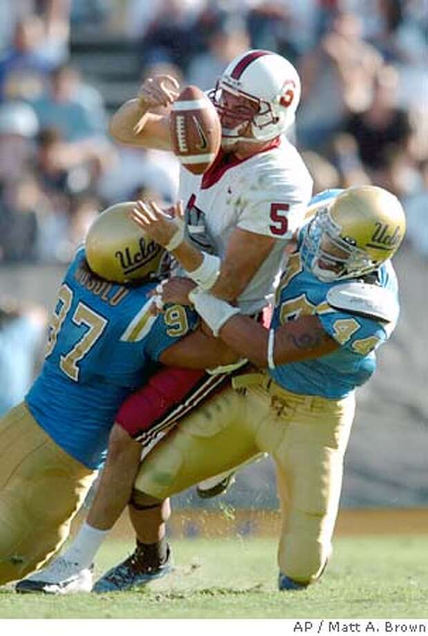 UCLA's C.J. Niusulu, left, and Bruce Davis bring down Stanford quarterback Trent Edwards and force a fumble during the fourth quarter at the Rose Bowl in Pasadena, Calif., Saturday, Oct. 30, 2004. Edwards recovered the fumble. (AP Photo/Matt A. Brown) Photo: MATT A. BROWN
