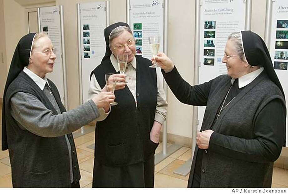 Sisters Sr. Imelda, Sr. Anna Mirian and Sr. Reverend Mother Bernadet, from left, at the catholic seminar in Traunstein, southern Germany, on Tuesday, April 19, 2005 toast to each other as they celebrate the election of German Cardinal Ratzinger, a frequent guest at the seminar, as the new pontiff. Cardinal Joseph Ratzinger of Germany, a longtime guardian of doctrinal orthodoxy, was elected the new pope Tuesday evening in the first Roman Catholic conclave of the new millennium. He chose the name Pope Benedict XVI. (AP Photo/Kerstin Joensson) Photo: KERSTIN JOENSSON