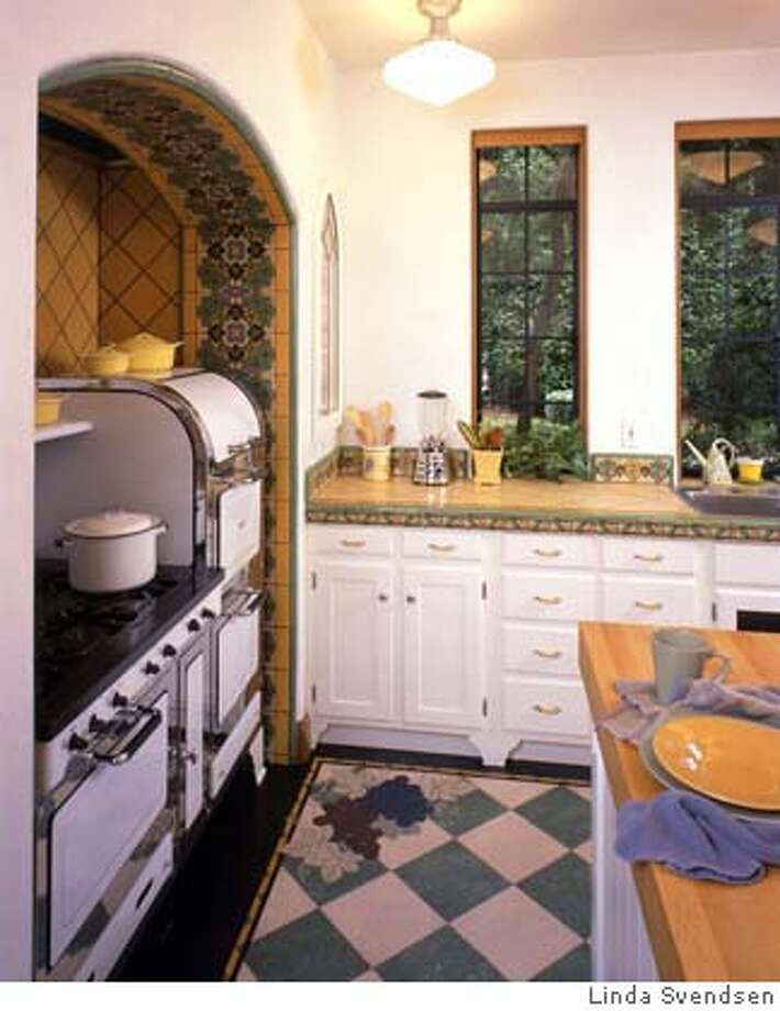 Linoleum floor with a custom inlay (design by Laurie Crogan), combined with reproduction Catalina tile, custom wood cabinets and a restored Magic Chef stove. Photo by Linda Svendsen