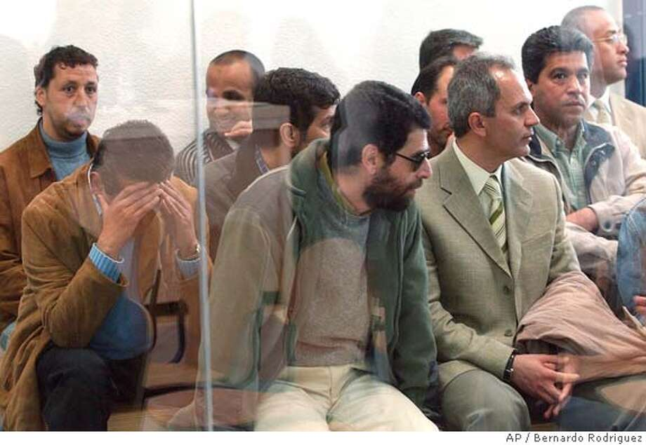 Unidentified Al-Qaida suspects sit behind a glass screen in a courthouse, a converted trade fair pavilion, in the Casa del Campo park in Madrid Friday April 22, 2005. Twenty-four suspected members of an Al-Qaida cell, mostly of Syrian and Moroccan origin, go on trial in Spain Friday, accused of using the country as a staging ground to plot the Sept. 11 terror attacks. (AP Photo / Pool, Bernardo Rodriguez) Photo: BERANDO RODRIGUEZ