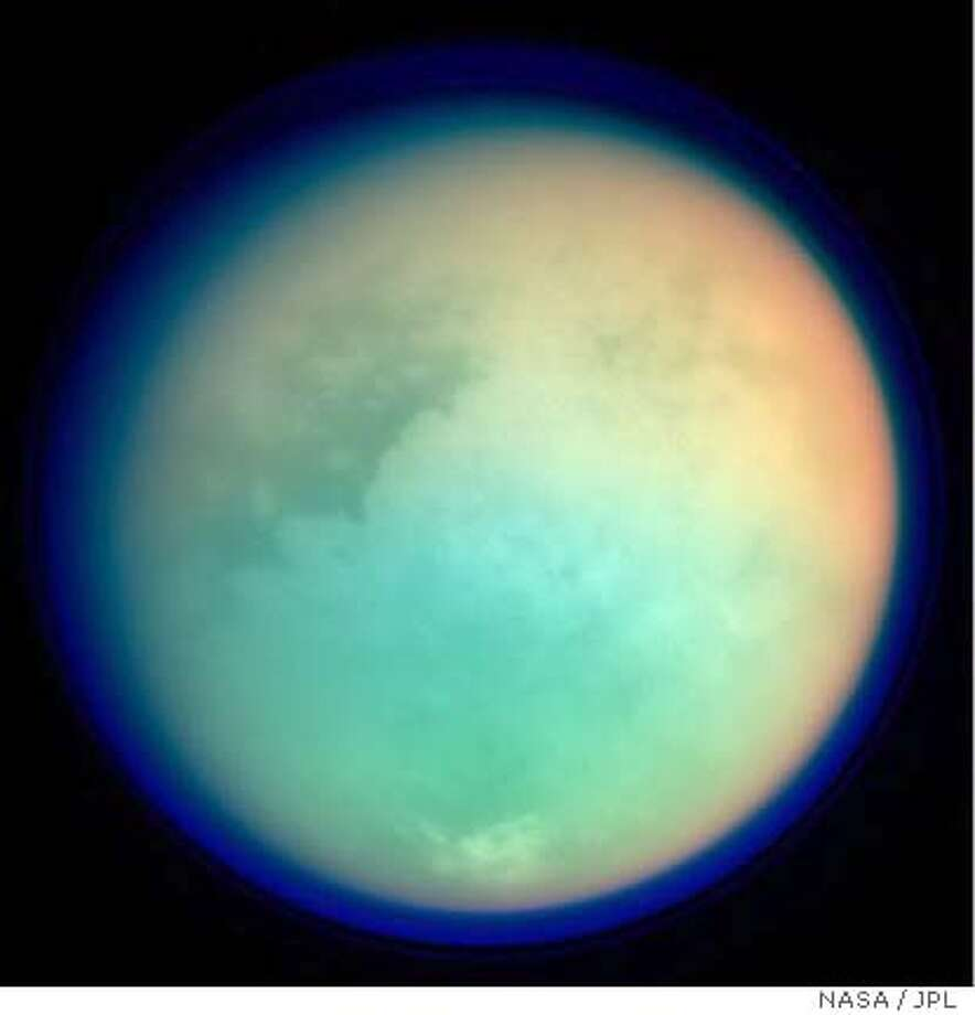 This image shows Titan in ultraviolet and infrared wavelengths. It was taken by Cassini's imaging science subsystem on Oct. 26, 2004, and is constructed from four images acquired through different color filters. Red and green colors represent infrared wavelengths and show areas where atmospheric methane absorbs light. These colors reveal a brighter (redder) northern hemisphere. Blue represents ultraviolet wavelengths and shows the high atmosphere and detached hazes. Titan has a gigantic atmosphere, extending hundreds of kilometers above the surface. The sharp variations in brightness on Titan's surface (and clouds near the south pole) are apparent at infrared wavelengths. The image scale of this picture is 6.4 kilometers (4 miles) per pixel. The Cassini-Huygens mission is a cooperative project of NASA, the European Space Agency and the Italian Space Agency. The Jet Propulsion Laboratory, a division of the California Institute of Technology in Pasadena, manages the Cassini-Huygens mission for NASA's Office of Space Science, Washington, D.C. The Cassini orbiter and its two onboard cameras, were designed, developed and assembled at JPL. The imaging team is based at the Space Science Institute, Boulder, Colo. For more information, about the Cassini-Huygens mission visit, http://saturn.jpl.nasa.gov and the Cassini imaging team home page, http://ciclops.org. Image Credit: NASA/JPL/Space Science Institute