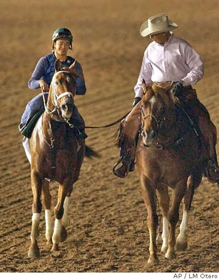 Azeri, left, topped by practice rider Yutta C.T. Lang is led by trainer D. Wayne Lukas, right, during an early morning workout at Lone Star Park Friday, Oct. 29, 2004, in preparation for Saturday's Breeders' Cup race in Grand Prairie, Texas. (AP Photo/LM Otero) Sports#Sports#Chronicle#10/30/2004#ALL#5star##0422439320 Photo: LM OTERO