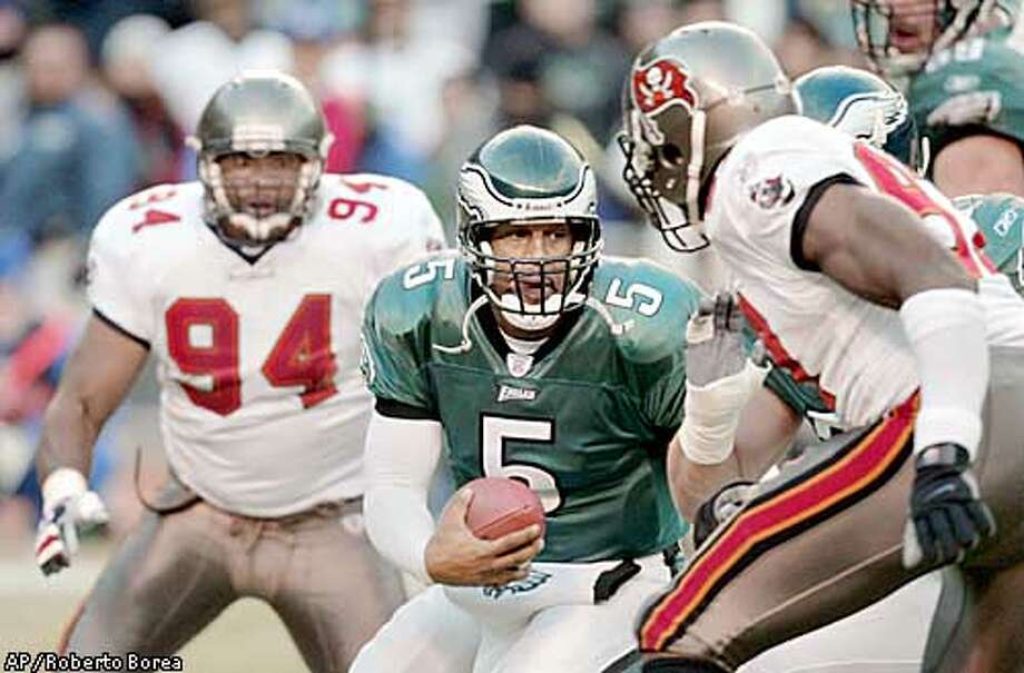 Philadelphia Eagles quarterback Donovan McNabb (5) challenges the defense of Tampa Bay Buccaneers' Simeon Rice, right, and Greg Spires (94) in the second quarter during the game at Veterans Stadium in Philadelphia, Sunday, Jan. 19, 2003. (AP Photo/Roberto Borea) Photo: ROBERTO BOREA