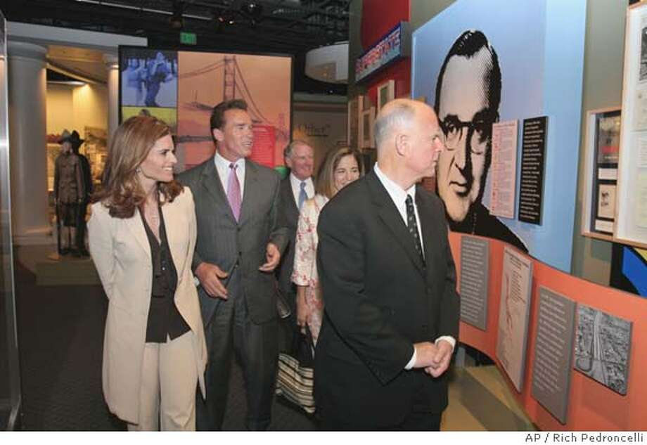"Oakland Mayor Jerry Brown, right, looks at one of the exhibits on his father, former California Gov. Pat Brown, at the California State Archives and the California State Museum for History, Women and the Arts in Sacramento, Calif., Wednesday, April 20, 2005. Brown toured the exhibit, titled ""SUPERSTATE: Pat Brown and a New California,"" with Maria Shriver, left, Gov. Arnold Schwarzenegger, second from left, Secretary of State Bruce McPherson, background, and Brown's fiancee' Anne Gust, second from right. The exhibit will open to the public on April 21 to coincide with Brown's 100th birthday. (AP Photo/Rich Pedroncelli) STAND ALONE Photo: RICH PEDRONCELLI"