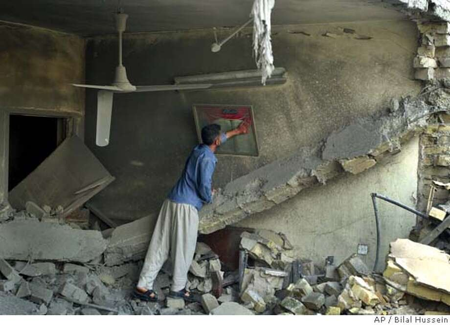 An Iraqi man cleans up a picture showing a page of the Quran, in a destroyed house in Fallujah, west of Baghdad, Iraq, early morning Friday, Oct 8, 2004 after an US air strike on the Sunni city. The US air strike on the rebel-held city of Fallujah killed 13 people and wounding 17 at a wedding party, according to hospital sources. With three months left before a landmark election, a group of hard-line Sunni Muslim clerics may hold the key to Iraq's future. The Association of Muslim Clerics, the most influential representative of Iraq's Sunni Arabs, is threatening to boycott the election if U.S. and Iraqi troops storm the insurgent stronghold of Fallujah. A large-scale boycott could push the country even deeper into chaos. (AP Photo/Bilal Hussein) Ran on: 10-24-2004  An Iraqi man cleans a picture in a house hit earlier this month in Fallujah, where U.S. forces continue operations. A suspected lieutenant to Abu Musab al-Zarqawi, has been apprehended in the area. Photo: BILAL HUSSEIN