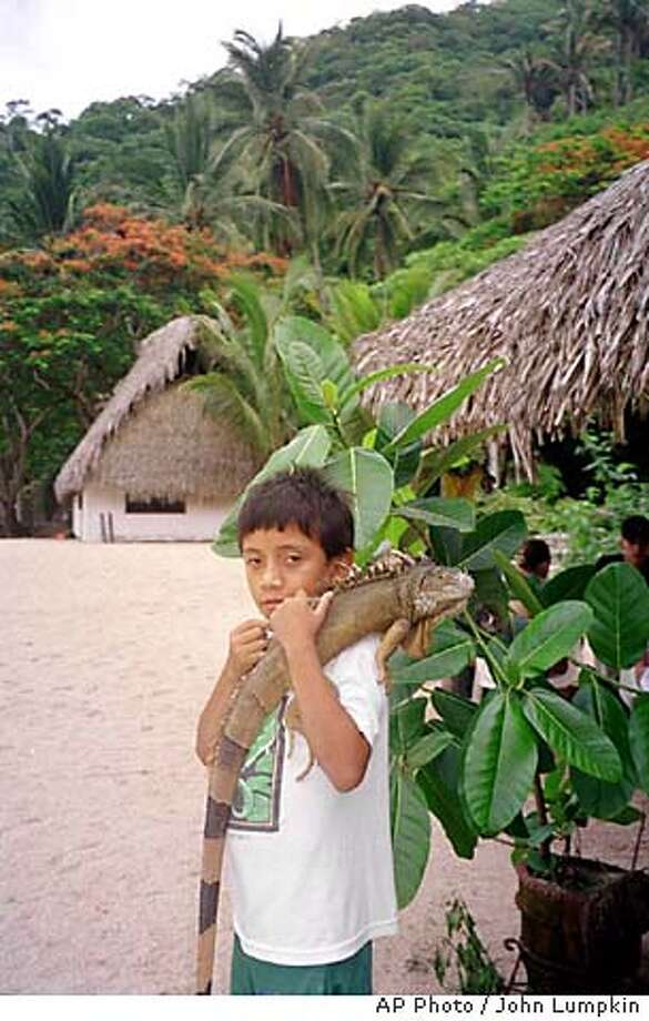 "FOR IMMEDIATE RELEASE--A young resident of Yelapa, a coastal village near Puerto Vallarta, Mexico, holds his pet iguana named ""Pancho,"" in this June 2000 photo. Yelapa, accessible only by boat, is a day's excursion for visitors to Puerto Vallarta and an overnight destination for more adventuresome tourists. (AP Photo/John Lumpkin) FOR IMMEDIATE RELEASE Travel#Travel#Chronicle#10/24/2004#ALL#Advance##0422423767 Photo: JOHN LUMPKIN"
