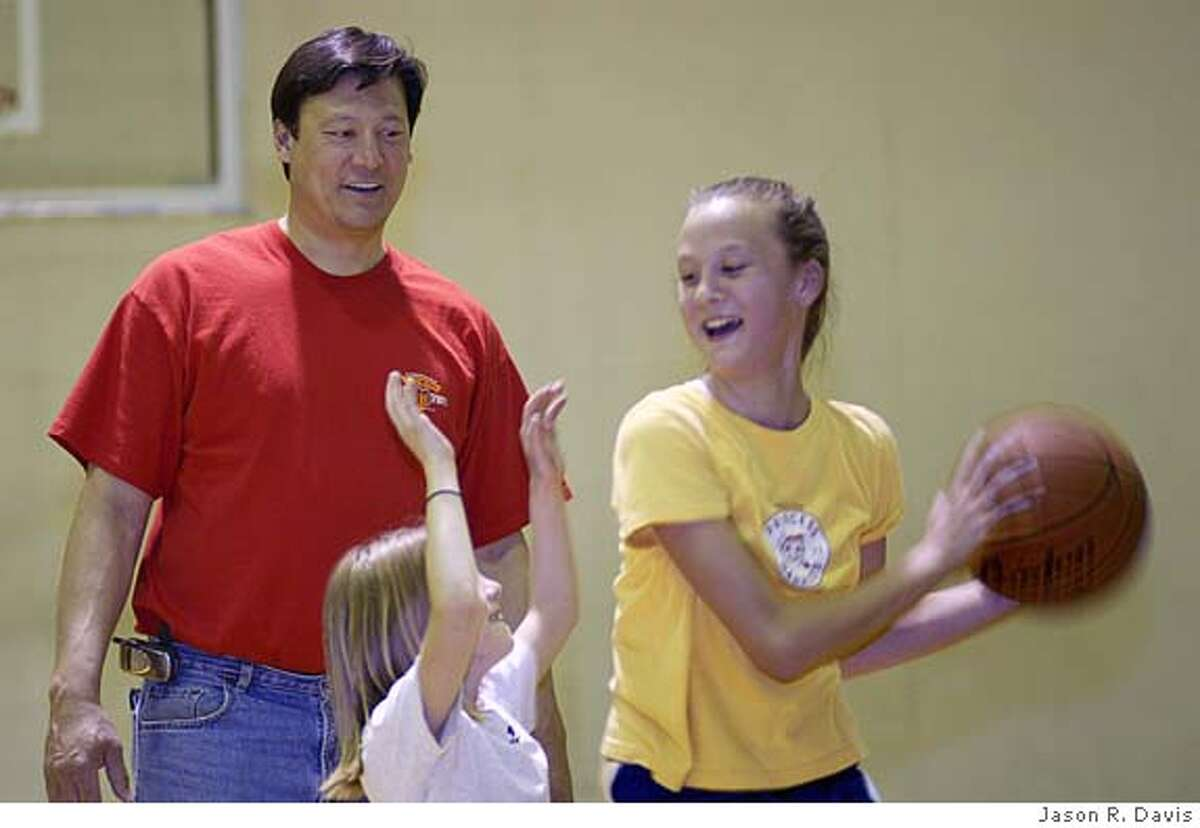 Atlee Hammaker, former San Francisco Giants pitcher, works with his daughters Anna, 8 (left) and Alesa, 13 (right) on their basketball skills at Karns High School in Knoxville, TN Thursday evening.