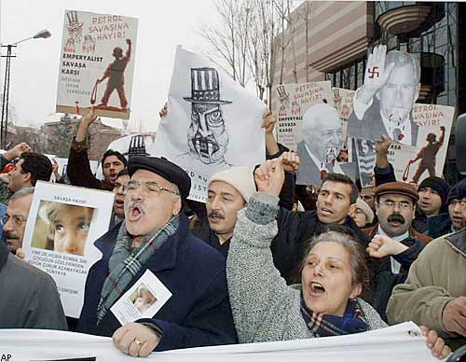 Turkish peace activists, holding banners with anti-war slogans, hold a demonstration in front of the U.S. Embassy in Ankara, Turkey on Friday Jan. 17, 2003. Facing stiff Turkish resistance, the United States is looking at scaling back its demand to base tens of thousands of soldiers in southern Turkey for a possible strike against Iraq, sources said Friday. Polls indicate that 80 percent of the country is against a war in Iraq. (AP Photo)
