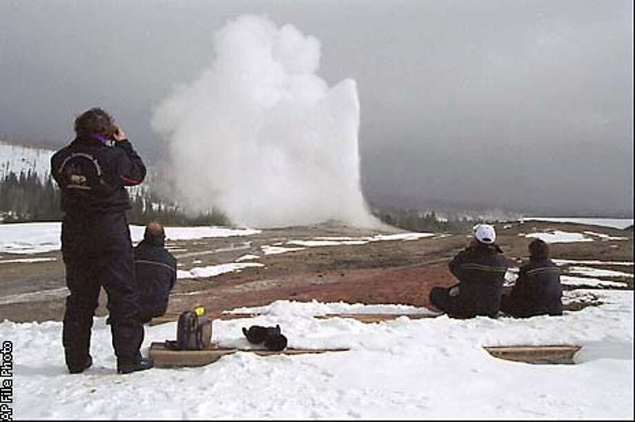 ADVANCE FOR WEEKEND EDITIONS MARCH 1-3--Four spectators enjoy the view of the steam from Old Faithful geyser in Yellowstone National Park Monday, Feb. 17, 1997. Sites like Old Faithful attract visitors all year long, and an estimated 140,000 people venture into the park each winter. (AP Photo/The Montana Standard, Perry Backus)