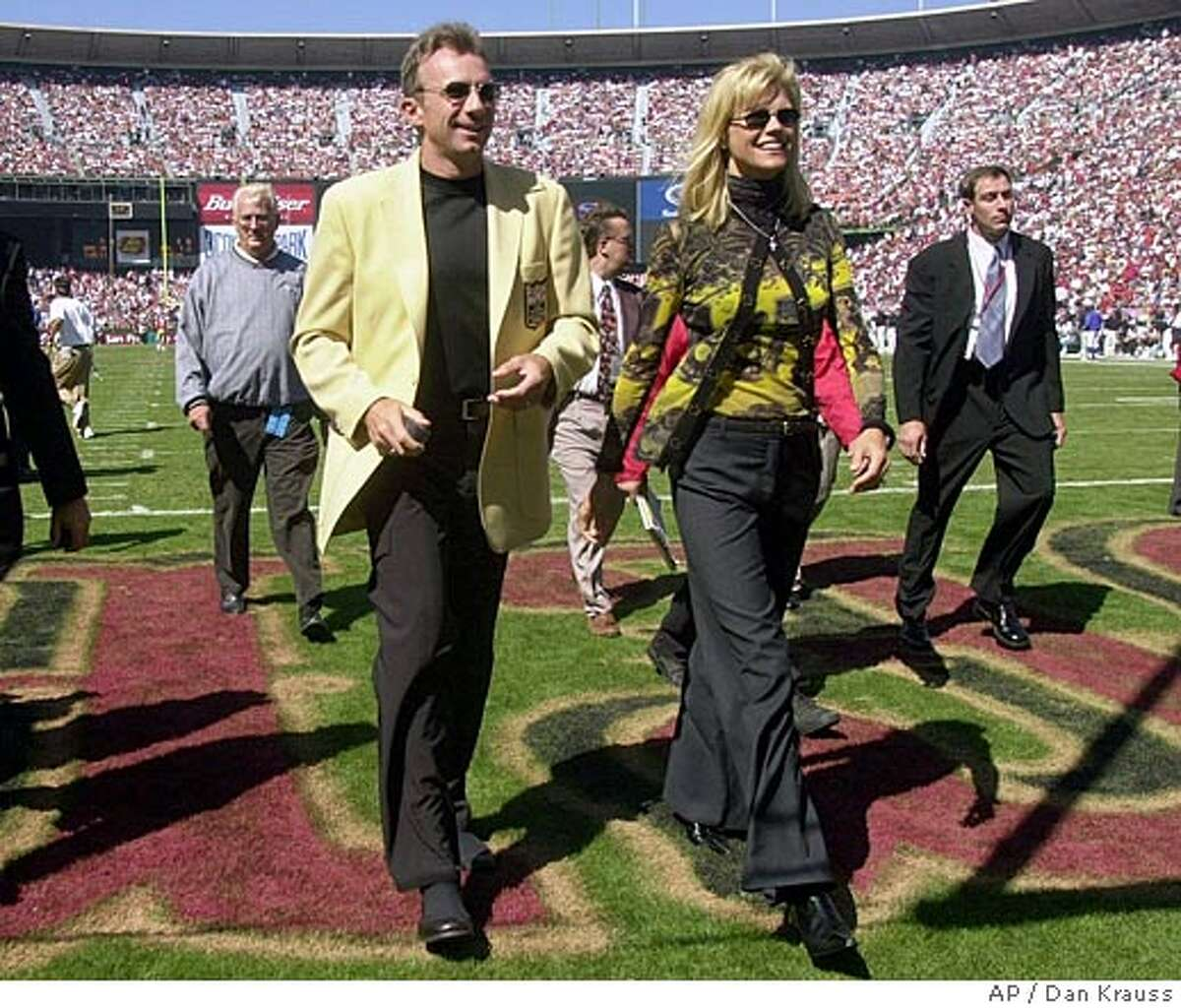 Former San Francisco 49ers quarterback Joe Montana walks off the field with his wife, Jennifer, after a halftime ceremony at 3Com Park in San Francisco honoring Montana and two other former 49ers Sunday, Sept. 10, 2000. (AP Photo/Dan Krauss)