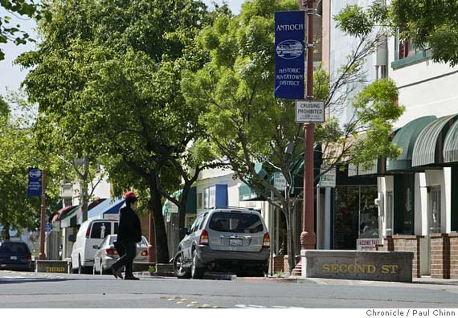 antioch_003_pc.jpg  Pedestrians cross an intersection in the heart of downtown Antioch. The historic Rivertown District on 4/13/05 in downtown Antioch, CA. Hoping to revitalize the sleepy town center, city officials are listening to several proposals from developers with renovation plans for the area.  PAUL CHINN/The Chronicle MANDATORY CREDIT FOR PHOTOG AND S.F. CHRONICLE/ - MAGS OUT Photo: PAUL CHINN