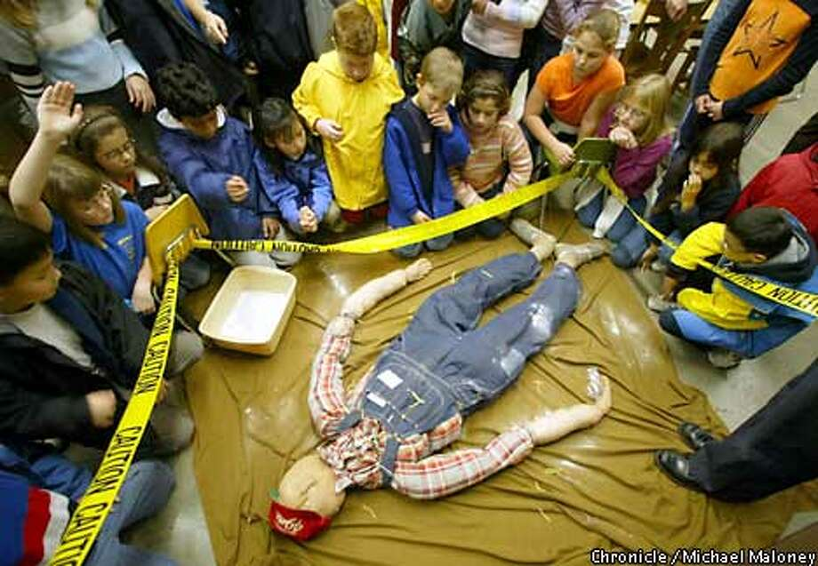 """Pupils from Danville's John Baldwin Elementary School gather around Clyde Peabody, a dummy corpse, to gather evidence in """"Who Done It?,"""" the Lawrence Hall of Science's forensic science class for third- through sixth-graders. Chronicle photo by Michael Maloney"""