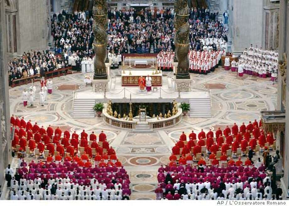 """In this photo made available by the Vatican newspaper L'Osservatore Romano, cardinals, in red, prelates, in purple and white, and faithful in background, attend a midmorning Mass in St. Peter's Basilica at the Vatican, Monday April 18, 2005, in their last public appearance before sequestering themselves inside the Sistine Chapel later in the day. Representing 52 countries, the 115 crimson-robed """"princes"""" of a church celebrated a midmorning Mass at St. Peter's Basilica before sequestering themselves in the Sistine Chapel at 4:30 p.m (1430 GMT) to start deliberating their choice of new pope.(AP Photo/L'Osservatore Romano,ho) Photo: OSSERVATORE ROMANO"""